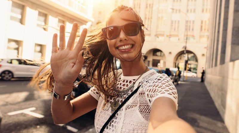 Young woman taking selfie in a street. Tourist posing for a selfie in a street. Vlogger recording content for her travel vlog.